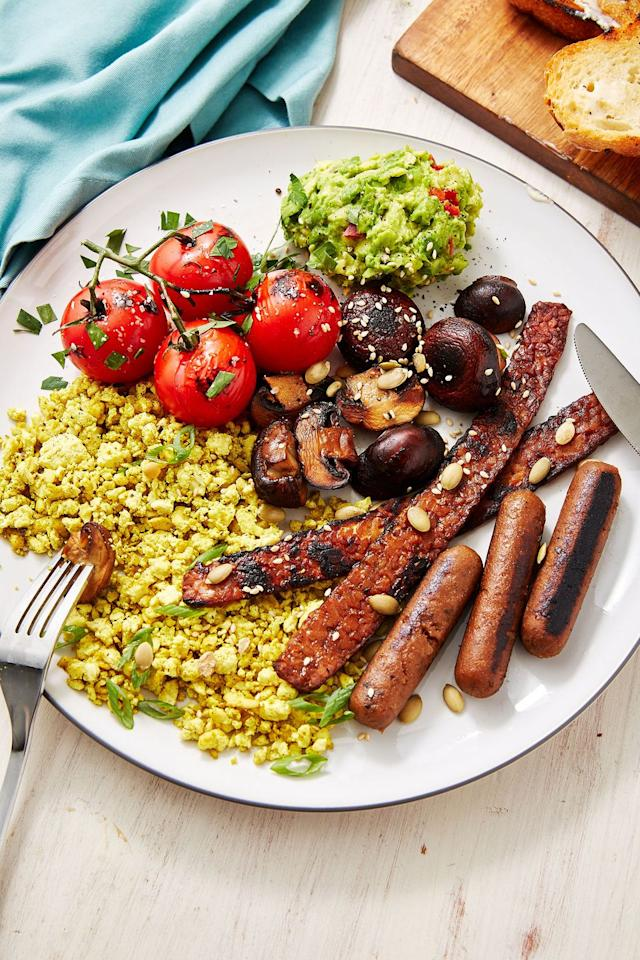 """<p>We've swapped the eggs for spicy scrambled tofu, swapped the meat for our fave vegan """"facon"""" and sausages, and even thrown in some smashed avo and griddled mushrooms and toms for even more flavour. </p><p>Get the <a href=""""https://www.delish.com/uk/cooking/recipes/a29572043/vegan-breakfast/"""" target=""""_blank"""">Vegan English Breakfast</a> recipe.</p>"""