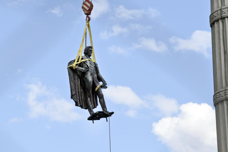 A statue of former U.S. vice president and slavery advocate John C. Calhoun is raised by crews after its removal from a 100-foot-tall monument on Wednesday, June 24, 2020, in Charleston, S.C.(AP Photo/Meg Kinnard)
