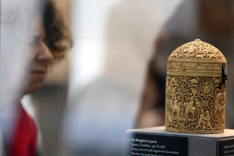 """A woman examines a box entitled """"Al-Mughira's pyxis"""" from Spain on September 17, 2012 in Paris, during a press visit of the new Department of Islamic Arts at the Louvre, the largest of its kind in Europe, with 3,000 artefacts on display, gathered from Spain to India and dating back to the seventh century AD. Intended to celebrate """"The Radiant Face of a Great Civilization"""" the 100-million-euro project - largely financed by donors from across the Islamic world - will be inaugurated by French President ahead of its official opening on September 18. AFP PHOTO / KENZO TRIBOUILLARD"""