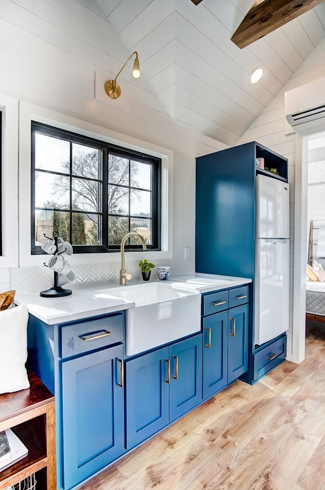 <p>For a home this small, you'd expect a tiny fridge and sink, but thankfully, this tiny home has neither issue. I mean, a farmhouse sink? Come on!</p>