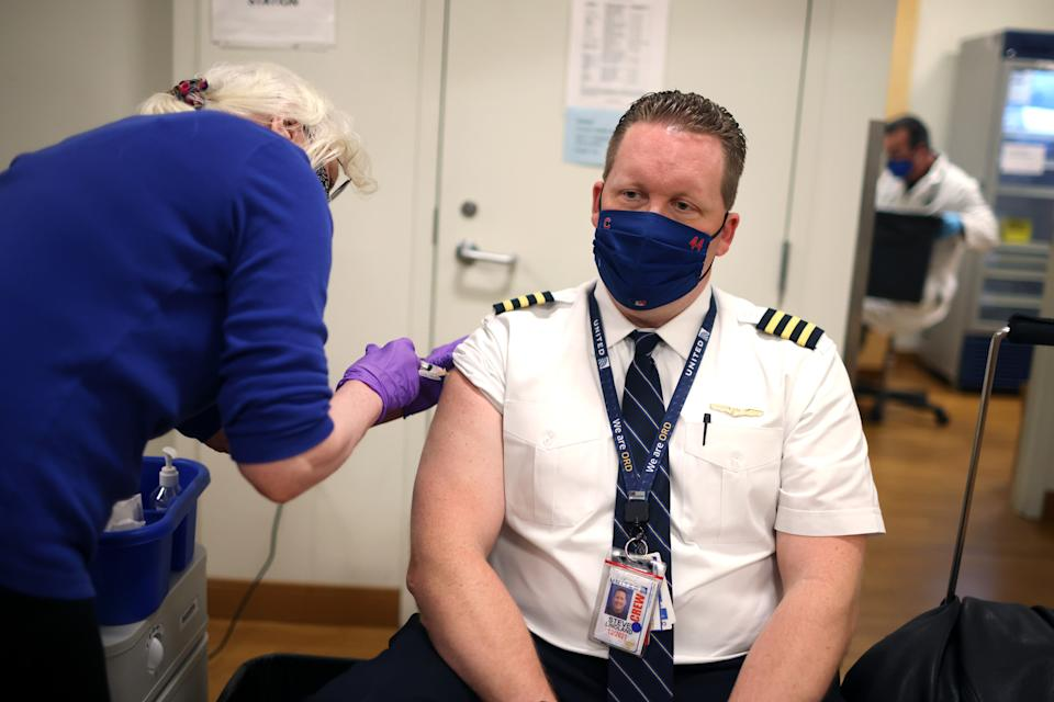CHICAGO, ILLINOIS - MARCH 09: United Airlines pilot Steve Lindland receives a COVID-19 vaccine from RN Sandra Manella at United's onsite clinic at O'Hare International Airport on March 09, 2021 in Chicago, Illinois. United has been vaccinating about 250 of their O'Hare employees at the clinic each day for the past several days.   (Photo by Scott Olson/Getty Images)
