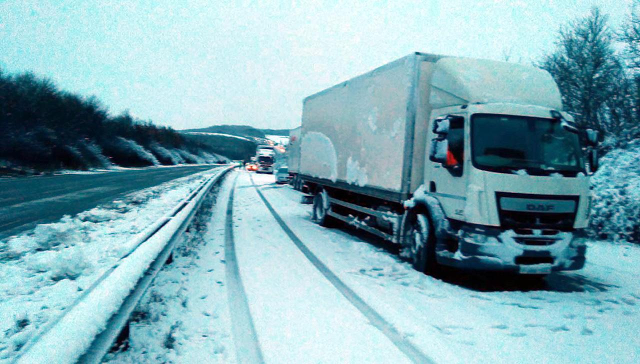 <p>Picture taken with permission from the twitter feed of @simontab of stuck lorries between J2 and J1 after overnight snow caused travel disruptions across parts of the UK. (PA) </p>