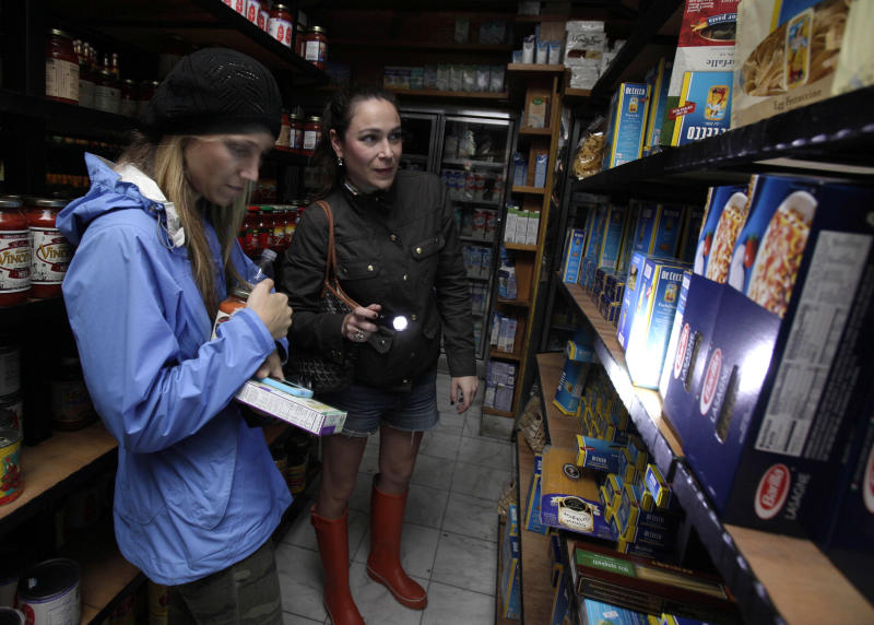 Two women shop for groceries by flashlight in the Tribeca neighborhood of New York, Tuesday, Oct. 30, 2012. ConEd cut power Moday to some neighborhoods served by underground lines as the advancing storm surge from Hurricane Sandy threatened to flood substations. Floodwaters later led to explosions that disabled a substation in Lower Manhattan, cutting power tens of thousands of customers south of 39th Street. (AP Photo/Richard Drew)