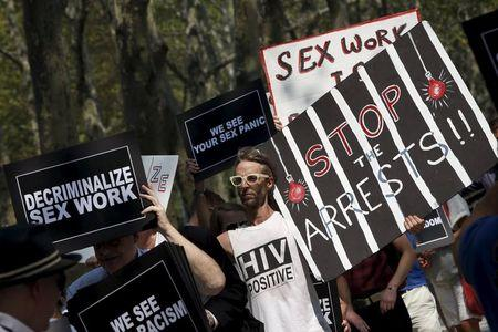 Demonstrators hold signs as they protest the arrests of male escort service Rentboy.com staffers outside United States Court in the Brooklyn borough of New York City, September 3, 2015. REUTERS/Mike Segar