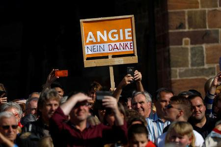 "Protesters hold a placard reading: ""Angie, no thanks"" as German Chancellor Angela Merkel, a top candidate of the Christian Democratic Union Party (CDU) for the upcoming general elections, speaks during an election rally in Fritzlar, Germany September 21, 2017. REUTERS/Kai Pfaffenbach"