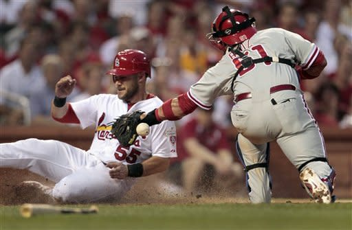 St. Louis Cardinals' Skip Schumaker, left, is safe at home as the throw gets away from Philadelphia Phillies catcher Carlos Ruiz during the third inning of a baseball game Thursday, May 24, 2012, in St. Louis. (AP Photo/Jeff Roberson)
