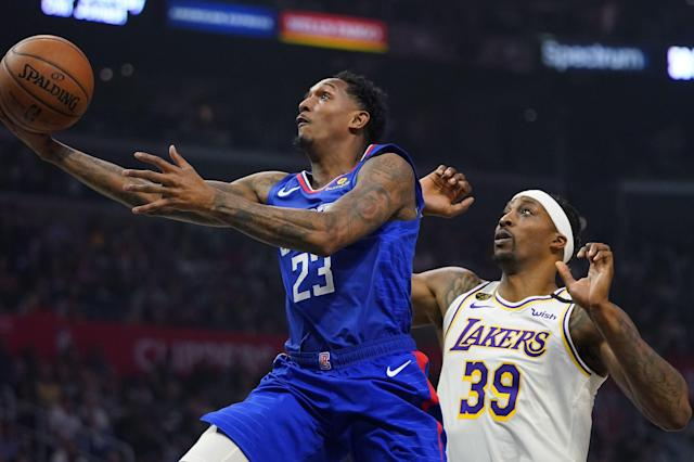 Los Angeles guard Lou Williams, left, shoots as Los Angeles Lakers center Dwight Howard defends during the first half of an NBA basketball game Sunday, March 8, 2020, in Los Angeles. (AP Photo/Mark J. Terrill)