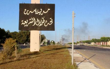 """A sign which reads in Arabic, """"The city of Sirte, under the shadow of Sharia"""" is seen as smoke rises in the background while forces aligned with Libya's new unity government advance on the eastern and southern outskirts of the Islamic State stronghold of Sirte, in this still image taken from video on June 9, 2016. Reuters TV/File Photo"""
