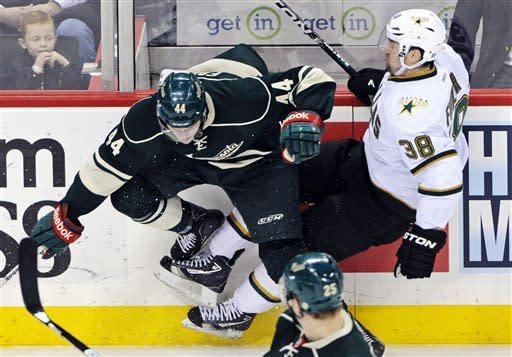 Minnesota Wild's Justin Falk, left, and Dallas Stars' Vernon Fiddler lose their footing in a collision along the boards in the first period of an NHL hockey game, Saturday, Jan. 21, 2012, in St. Paul, Minn. (AP Photo/ Jim Mone)