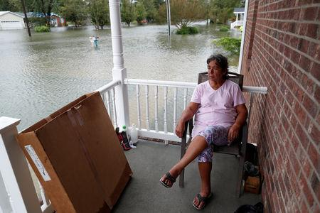 After just rebuilding her home from the floods of 2016, Willie Allen watches the water rise from her porch during Tropical Storm Florence in Lumberton, North Carolina, U.S. September 16, 2018.  REUTERS/Randall Hill
