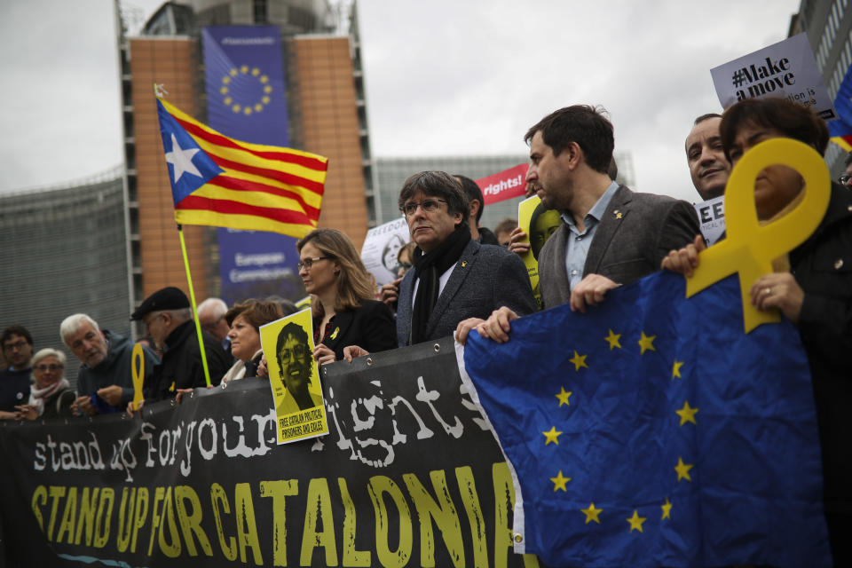 Catalonia's former regional president Carles Puigdemont, fourth right, hold a banner with others during a protest in front of the European Commission headquarters in Brussels, Tuesday Oct. 15, 2019. New disruptions to Catalonia's transportation network on Tuesday followed a night of clashes between activists and police over the conviction of separatist leaders, as Spanish authorities announced an investigation into the group organizing the protests. (AP Photo/Francisco Seco)