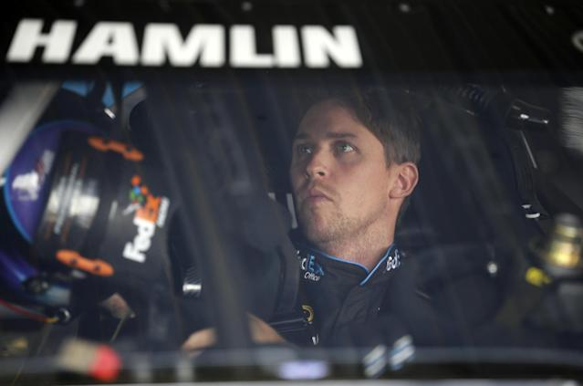 Denny Hamlin sits in his race car in the garages during practice for Sunday's NASCAR Sprint Cup Series auto race at Pocono Raceway, Friday, Aug. 1, 2014, Long Pond, Pa. (AP Photo/Mel Evans)