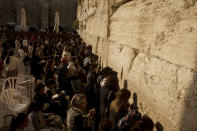 Worshippers pray in the women's section of the Western Wall, the holiest site where Jews can pray, in the shadow of the Mughrabi Bridge, a wooden pedestrian bridge connecting the wall to the Al Aqsa Mosque compound, in Jerusalem's Old City, Tuesday, July 20, 2021. The rickety bridge allowing access to Jerusalem's most sensitive holy site is at risk of collapse, according to experts. But the flashpoint shrine's delicate position at ground-zero of the Israeli-Palestinian conflict has prevented its repair for more than a decade. (AP Photo/Maya Alleruzzo)