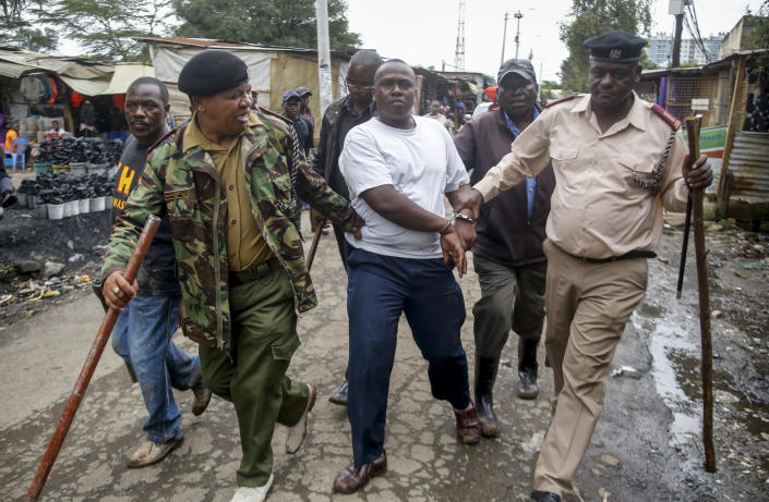 Security forces arrest a man for operating a restaurant serving food to customers eating on the premises, which has been prohibited and only takeaways are allowed under measures aimed at halting the spread of the new coronavirus, in Nairobi, Kenya Friday, March 27, 2020. The new coronavirus causes mild or moderate symptoms for most people, but for some, especially older adults and people with existing health problems, it can cause more severe illness or death. (AP Photo/Brian Inganga)