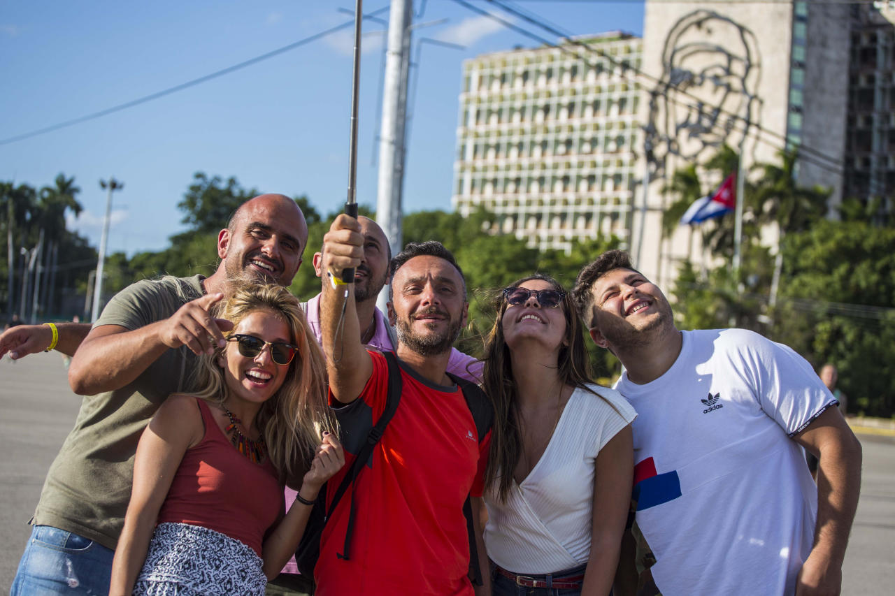 "Tourists take selfies with an iconic image of Cuba's revolutionary hero Ernesto ""Che"" Guevara in the background, at Revolution Square near the Ministry of Interior in Havana, Cuba, Sunday, Nov. 27, 2016. Cuba's government declared nine days of national mourning after Cuban leader Fidel Castro died Friday and this normally vibrant city has been notably subdued. As Cuba prepares a massive commemoration for Castro, tens of thousands of high-season travelers have found themselves accidental witnesses to history and in the middle of a somber city that's little like its usual exuberant self. (AP Photo/Desmond Boylan)"