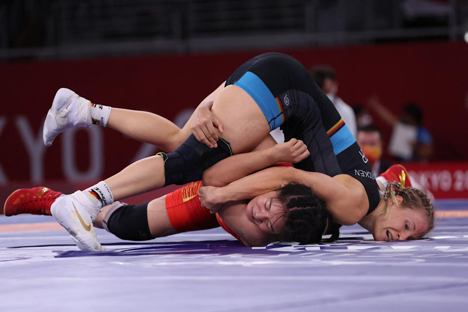 <p>Germany's Aline Rotter Focken (blue) wrestles China's Zhou Qian in their women's freestyle 76kg wrestling early round match during the Tokyo 2020 Olympic Games at the Makuhari Messe in Tokyo on August 1, 2021. (Photo by Jack GUEZ / AFP)</p>