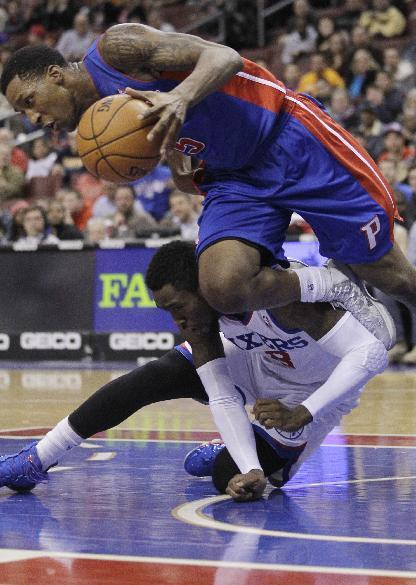 Detroit Pistons' Kentavious Caldwell-Pope, top, stumbles over Philadelphia 76ers' Tony Wroten in the first half of an NBA basketball game on Friday, Jan. 10, 2014, in Philadelphia. (AP Photo/Laurence Kesterson)