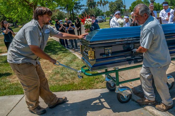 """Cemetery workers carry the elegant casket for Dung Tan Nguyen who was a local member of the Vietnamese community and a musician on Wednesday, May 6, 2020, during the coronavirus outbreak. """"It would have been the family but there weren't enough men to carry it,"""" said his daughter-in-law Trang Nguyen as she explained the COVID-19 restrictions on social distancing at Sacramento Memorial Lawn prevented many from attending the funeral."""