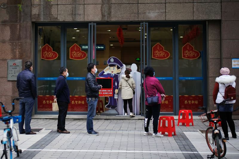People wearing face masks practise social distancing as they wait outside a Hankou Bank branch in Wuhan