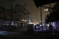People and auto rickshaws are silhouetted on vehicles headlights on a dark street during widespread power outages in Rawalpindi, Pakistan, Sunday, Jan. 10, 2021. Pakistan's national power grid experienced a major breakdown late night on Saturday, leaving millions of people in darkness, local media reported. (AP Photo/Anjum Naveed)