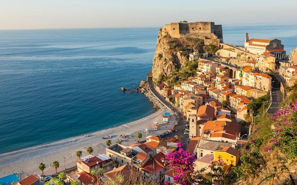 castle on outcrop above the sea next to colourful houses - Peter Adams/Getty Images