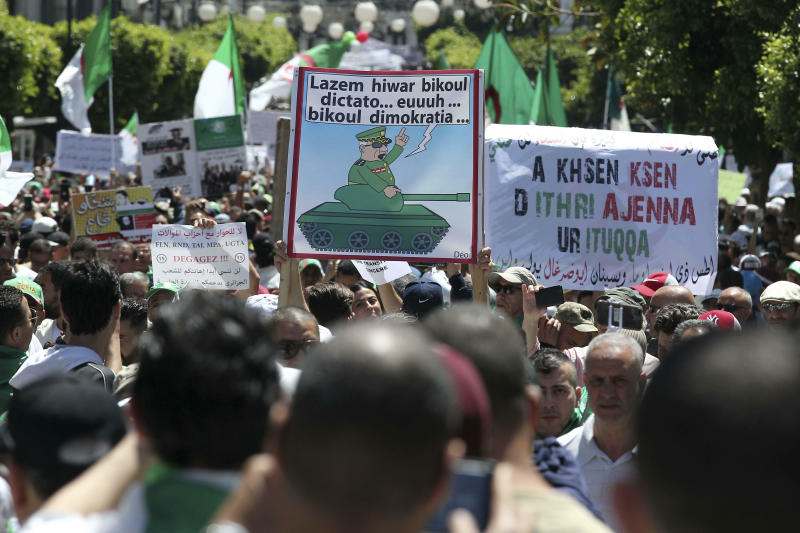 "Algerian protesters gather during an anti-government demonstration in the centre of the capital Algiers, Algeria, Friday, May 31, 2019. Banner in Arabic mocking army chief says ""There must be a dialogue, as dictator.. democratically as possible."" (AP Photo/Fateh Guidoum)"