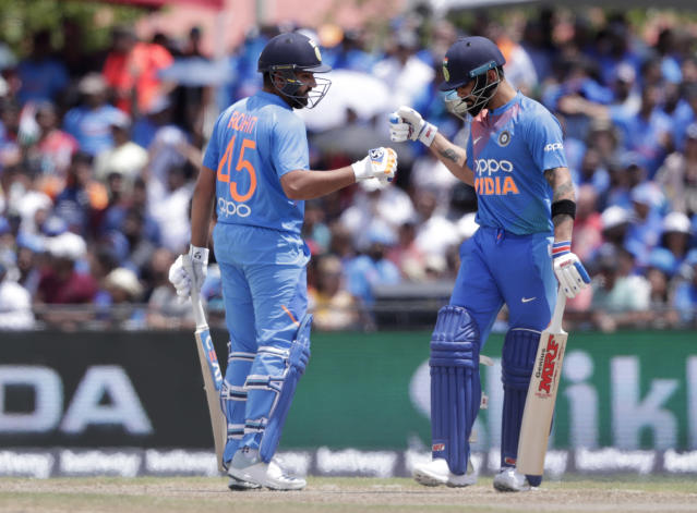 India's Rohit Sharma, left, bumps fist with Virat Kohli, right, during the first Twenty20 international cricket match against the West Indies, Saturday, Aug. 3, 2019, in Lauderhill, Fla. India won by four wickets. (AP Photo/Lynne Sladky)