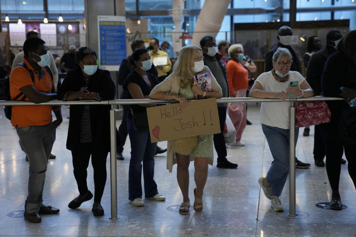 Mothers Debbie Greaves, center, and Karen Tyler, right, who don't know each other, wait to greet their sons arriving on different flights at Terminal 5 of Heathrow Airport in London, Monday, Aug. 2, 2021. Travelers fully vaccinated against coronavirus from the United States and much of Europe were able to enter Britain without quarantining starting today, a move welcomed by Britain's ailing travel industry. (AP Photo/Matt Dunham)