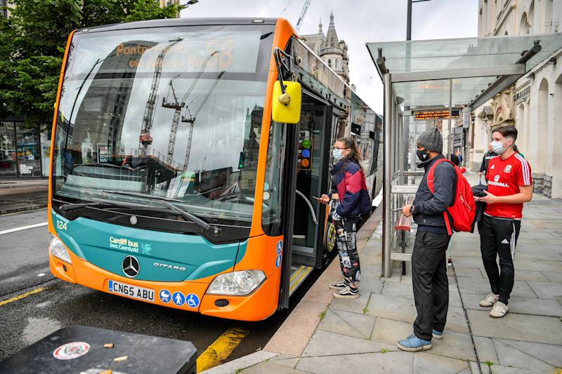 Passengers queue to board a bus in Cardiff as face coverings become mandatory on public transport in Wales to help prevent the spread of coronavirus. (Photo by Ben Birchall/PA Images via Getty Images)