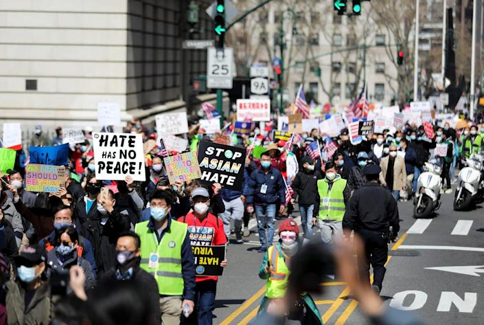 People march with signs that say 'Stop Asian Hate'