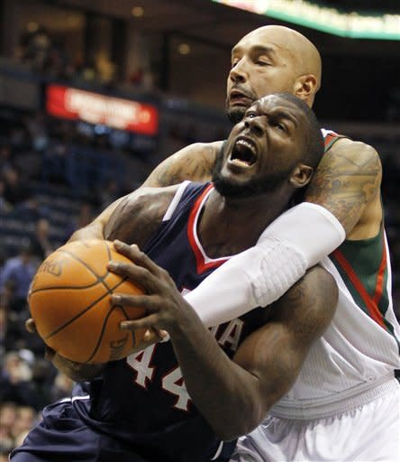 Atlanta Hawks' Ivan Johnson (44) is fouled by Milwaukee Bucks' Drew Gooden, right, during the first half of an NBA basketball game Monday, Jan. 23, 2012, in Milwaukee. (AP Photo/Jeffrey Phelps)