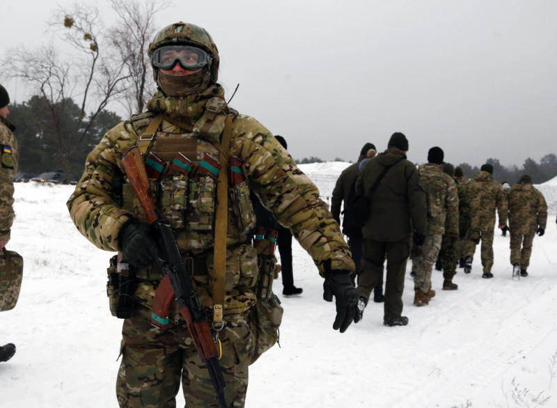 A security officer covers the back of Ukrainian President Petro Poroshenko during military drills in base Honcharivske, Chernihiv region, Ukraine, Monday, Dec. 3, 2018. President Petro Poroshenko says Russia has deployed a large number of troops along its border with Ukraine. He warns that Russia intends to push further inland into Ukraine following last week's naval clash between their forces in the Black Sea. Russia has already annexed the Black Sea peninsula of Crimea.(AP Photo/Efrem Lukatsky)