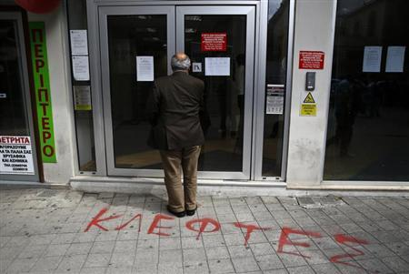 A depositor waits to enter a Laiki Bank branch in Nicosia