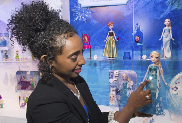 A demonstrator plays with a play-a-melody Elsa doll at the American International Toy Fair (AP Images)