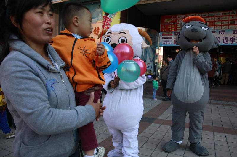 "In this photo taken Sunday, Oct. 2, 2011, a woman and child gather near mascots of characters from the cartoon ""Pleasant Goat and Big Big Wolf"" on a street in Beijing, China. A Chinese court has ruled the producer of the hit kids cartoon was partly to blame for the injuries suffered by two children when their friend tied them to a tree and set them on fire in an imitation of a scene from the show, state media reported Wednesday, Dec 18, 2013. (AP Photo/Ng Han Guan)"