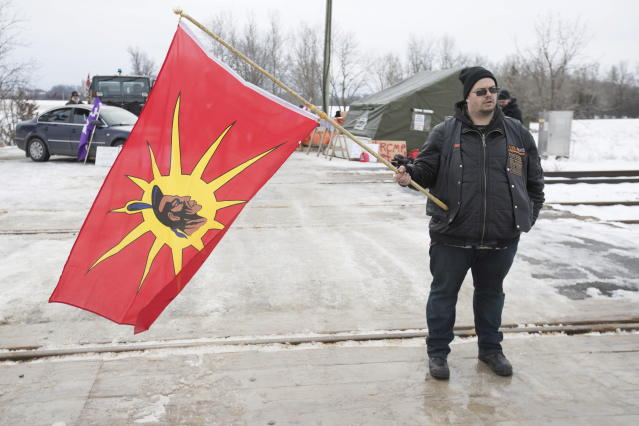 A man holds a warrior flag during the sixth day of blockade of the CN/VIA train tracks in Tyendinaga Mohawk Territory, near Belleville, Ont., on Tuesday, Feb. 11, 2020, in support of Wet'suwet'en's blockade of a natural gas pipeline in northern B.C. (Lars Hagberg/The Canadian Press via AP)