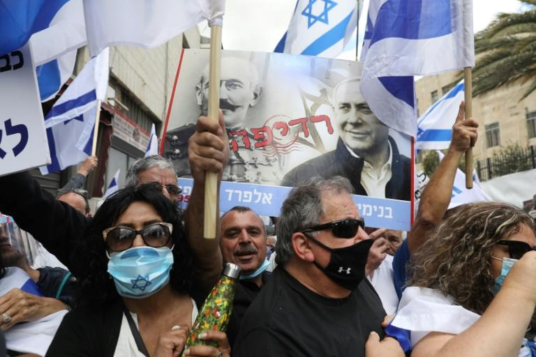 Supporters of Netanyahu hold up a poster depicting French officer Alfred Dreyfus who was unjustly convicted of treason in a trial that divided France in the late 19th century (AFP Photo/Menahem KAHANA)