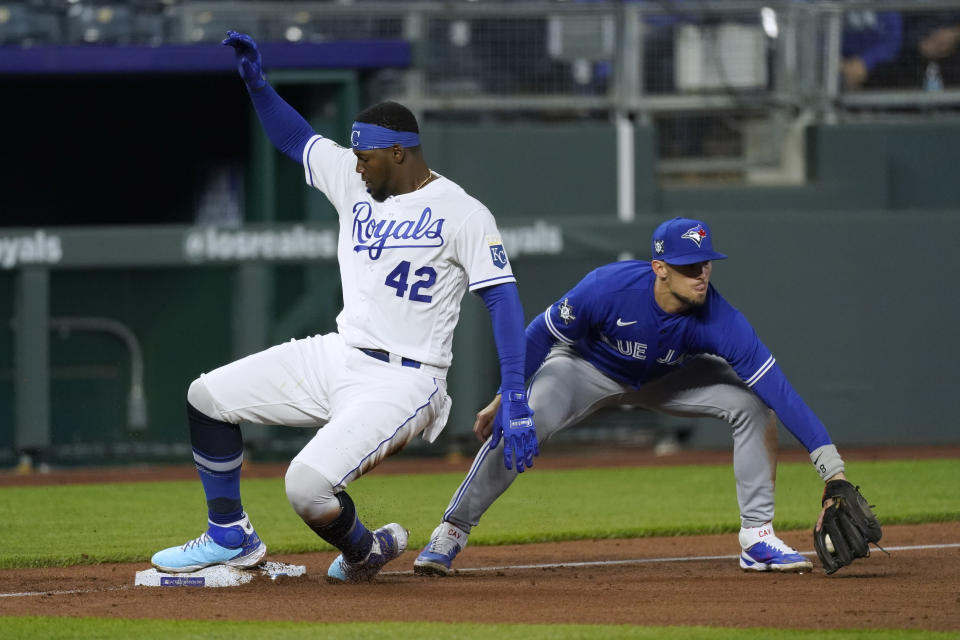 Kansas City Royals' Jorge Soler, left, beats the tag by Toronto Blue Jays third baseman Cavan Biggio to advance to third on a flyout by Michael A. Taylor during the fourth inning of a baseball game Thursday, April 15, 2021, in Kansas City, Mo. (AP Photo/Charlie Riedel)