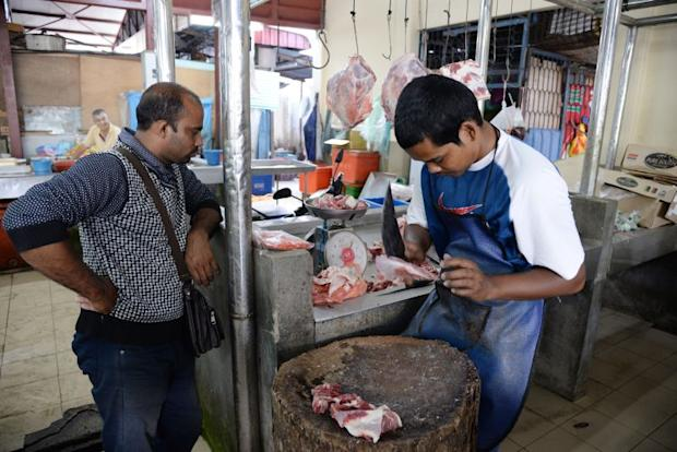 Mohd Faiz Md Nasir chopping up some mutton for a customer.