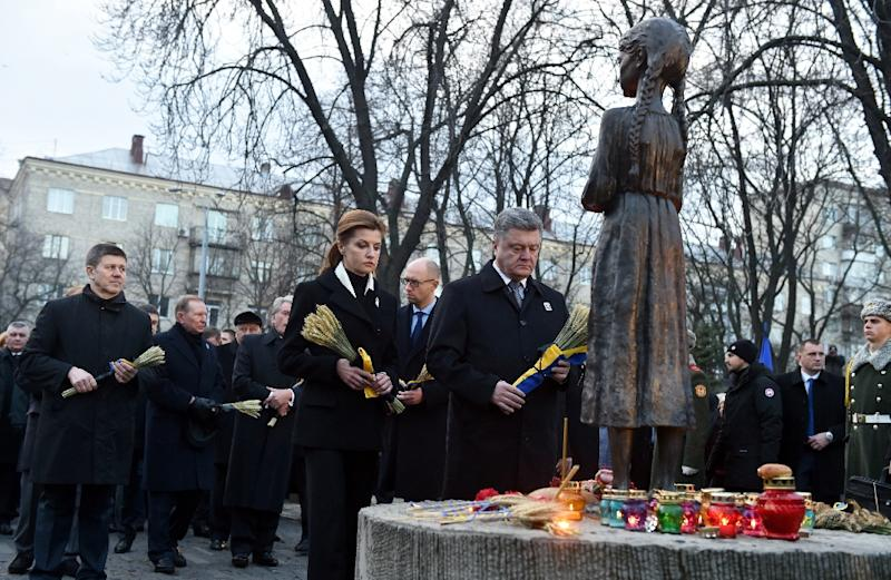 Ukrainian President Petro Poroshenko (C) and his wife Maryna lay spikelets of wheat in memory of the victims during a ceremony at the Holodomor famine memorial in Kiev on November 28, 2015