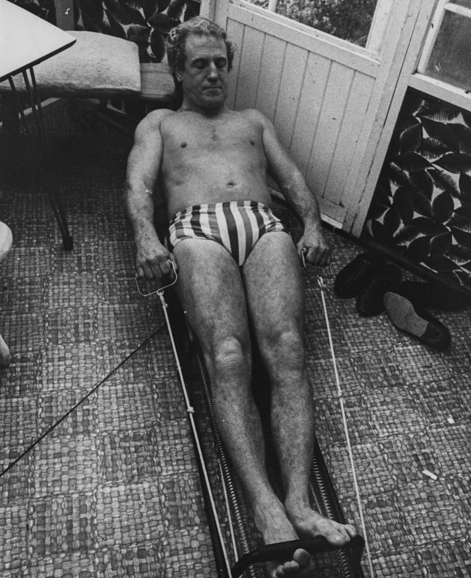 <p>Thanks to all of the new fitness inventions, working out at home was easier than ever before. Here, British wrestler Jackie Pallo works on his strength training before a match. </p>