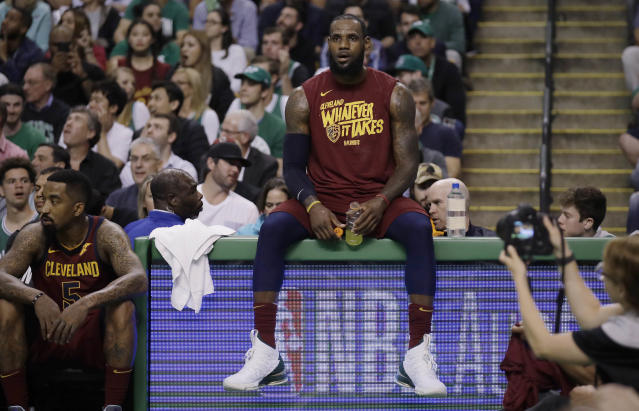 FILE - In this Tuesday, May 15, 2018, file photo, Cleveland Cavaliers forward LeBron James sits on the scorer's table during a timeout in the first half in Game 2 of the team's NBA basketball Eastern Conference finals against the Boston Celtics in Boston. James has twice come back from a 2-0 deficit in the NBA playoffs. He's going to need to do it three times to make the NBA Finals for the eighth straight year, down 2-0 to the Celtics. (AP Photo/Charles Krupa, File)