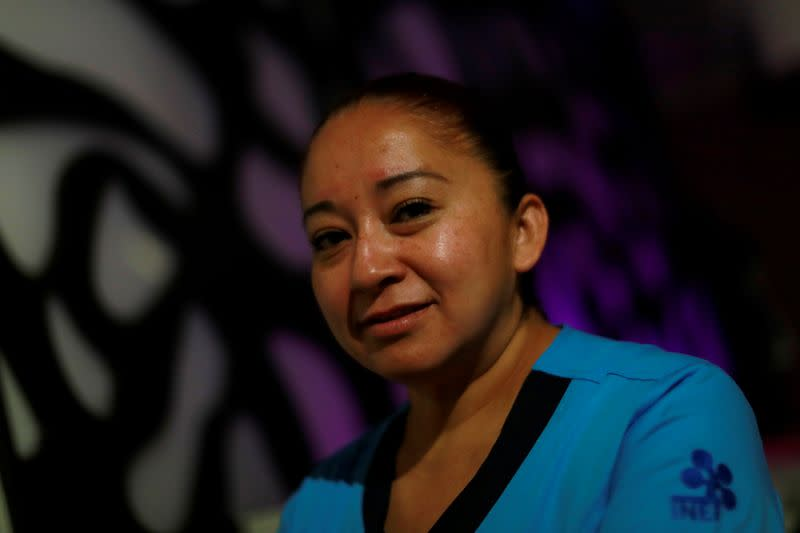 Nurse Gisela Hernandez, who has stayed away from her children for nearly two months to avoid infecting them because she feels inadequately protected, poses for a photograph at her hotel room in Mexico City