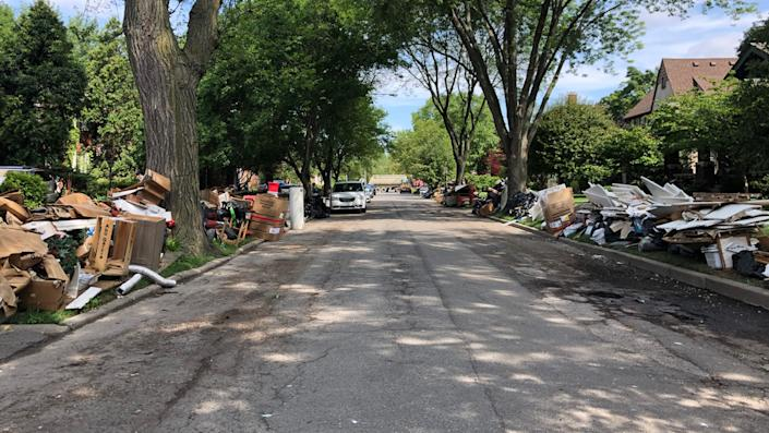 Residents in Grosse Pointe, Mich., try to clear out the damage on July 10, weeks after the first flooding.