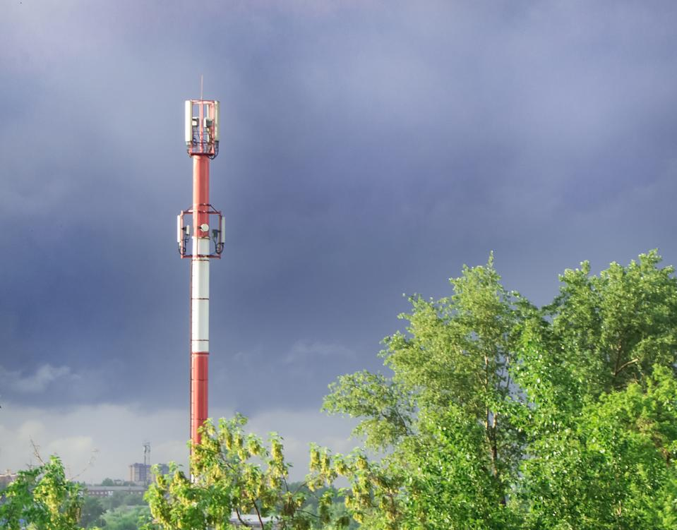 High tower of the GSM transmitter station in the evening against the background of blue sky and trees, in summer, after rain.
