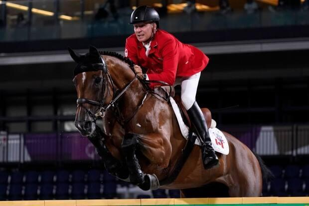 Canada's Mario Deslauriers, seen competing at the Tokyo Olympics, finished fifth at the CP International show jumping competition at Spruce Meadows in Calgary on Sunday.   (Carolyn Kaster/Associated Press  - image credit)