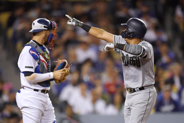 San Diego Padres' Christian Villanueva, right, gestures as he scores after hitting a two-run home run, as Los Angeles Dodgers catcher Yasmani Grandal stands at the plate during the sixth inning of a baseball game Saturday, May 26, 2018, in Los Angeles. (AP Photo/Mark J. Terrill)
