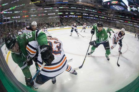 Dec 3, 2018; Dallas, TX, USA; Dallas Stars right wing Brett Ritchie (25) and center Mattias Janmark (13) and Edmonton Oilers defenseman Matthew Benning (83) and right wing Patrick Russell (52) fight for the puck during the second period at the American Airlines Center. Mandatory Credit: Jerome Miron-USA TODAY Sports