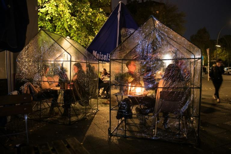 Guests sit in plastic tents as a protection measure against Covid-19 at a coffee shop and bar in Berlin