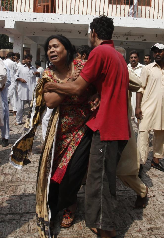 A man comforts a woman as she cries over the death of her relatives at the site of a blast at a church in Peshawar